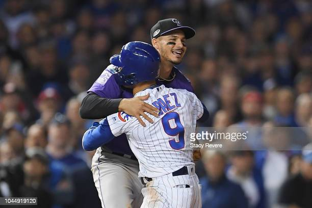 Javier Baez of the Chicago Cubs hugs Nolan Arenado of the Colorado Rockies in the eleventh inning during the National League Wild Card Game at...