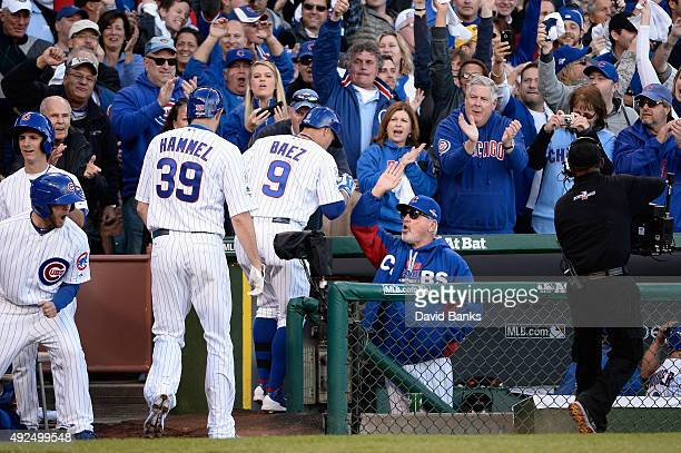 Javier Baez of the Chicago Cubs is congratulated by manager Joe Maddon of the Chicago Cubs after hitting a threerun home run in the second inning...