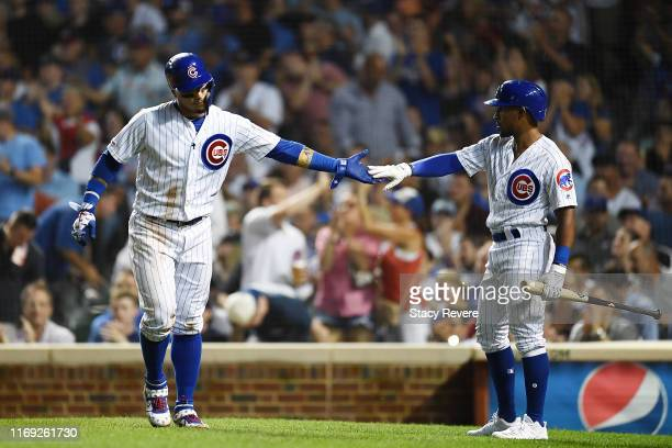 Javier Baez of the Chicago Cubs is congratulated by Tony Kemp after scoring a run during the fifth inning against the San Francisco Giants at Wrigley...