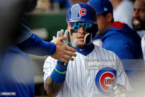Javier Baez of the Chicago Cubs is congratulated in the dugout after scoring against the Pittsburgh Pirates on an RBI single by Kyle Schwarber during...