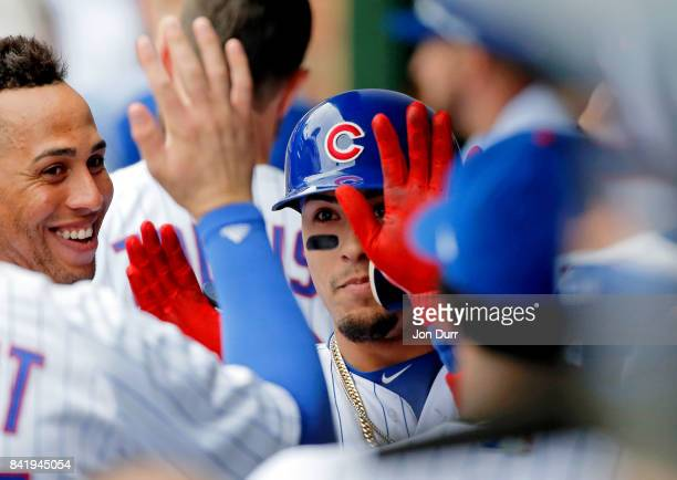 Javier Baez of the Chicago Cubs is congratulated in the dugout after hitting a home run against the Atlanta Braves during the third inning at Wrigley...