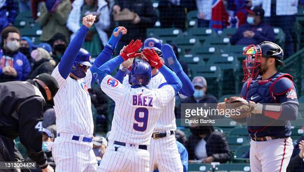 Javier Baez of the Chicago Cubs is greeted after hitting a three run home run against the Atlanta Braves during the third inning at Wrigley Field on...