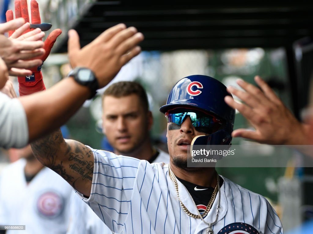 Javier Baez #9 of the Chicago Cubs is greeted by teammates after stealing home plate as James McCann #34 of the Detroit Tigers makes a late tag during the fourth inning on July 4, 2018 at Wrigley Field in Chicago, Illinois.