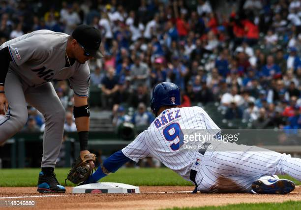 Javier Baez of the Chicago Cubs is safe at third base as Miguel Rojas of the Miami Marlins makes a late tag during the first inning at Wrigley Field...