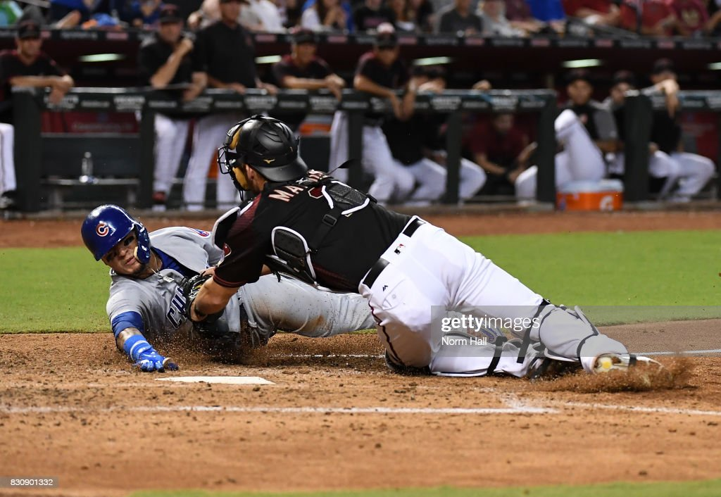 Javier Baez #9 of the Chicago Cubs is tagged out at home plate by Jeff Mathis #2 of the Arizona Diamondbacks during the fifth inning at Chase Field on August 12, 2017 in Phoenix, Arizona.