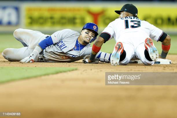 Javier Baez of the Chicago Cubs is tagged out by Starlin Castro of the Miami Marlins during the sixth inning against the Miami Marlins at Marlins...