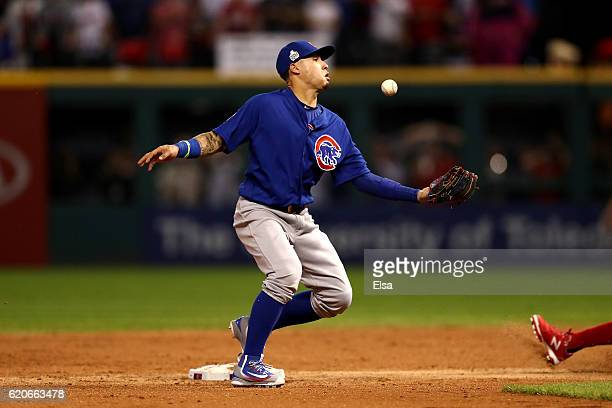 Javier Baez of the Chicago Cubs makes a missed catch error as Carlos Santana of the Cleveland Indians is safe at second base during the third inning...