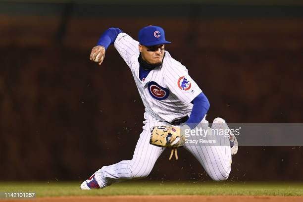 Javier Baez of the Chicago Cubs makes a throw to first base during the fourth inning against the Pittsburgh Pirates at Wrigley Field on April 11 2019...