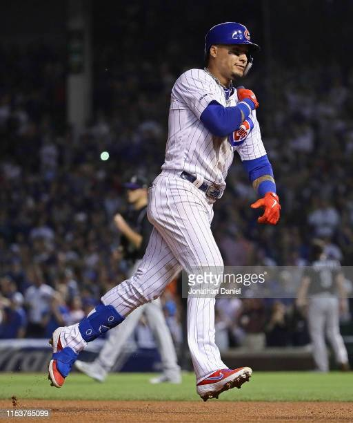 Javier Baez of the Chicago Cubs pounds his shoulder as he runs the bases after hitting a two run home run in the 6th inning against the Colorado...