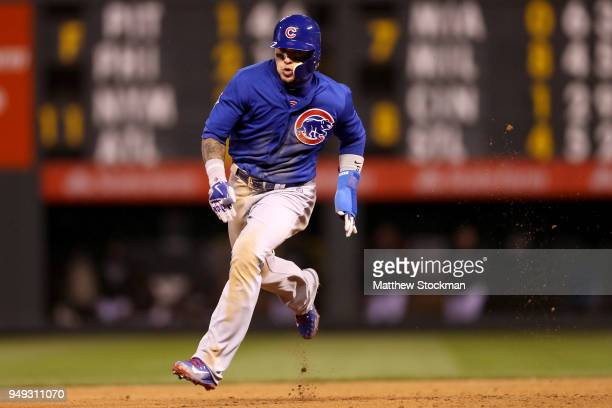 Javier Baez of the Chicago Cubs races to third base on a Kris Bryant double in the sixth inning against the Colorado Rockies at Coors Field on April...
