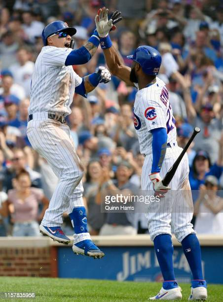 Javier Baez of the Chicago Cubs reacts with Jason Heyward of the Chicago Cubs after his three run home run in the eight inning against the New York...