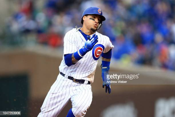Javier Baez of the Chicago Cubs rounds second to score a run during the third inning against the St Louis Cardinals at Wrigley Field on September 30...