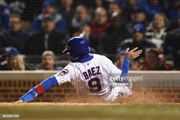 Javier Baez of the Chicago Cubs scores a run during the sixth inning of a game against the Pittsburgh Pirates at Wrigley Field on April 11 2018 in...