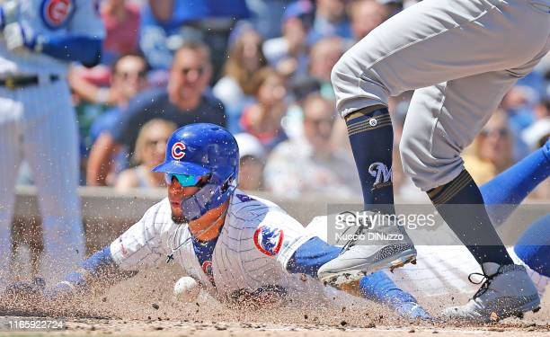 Javier Baez of the Chicago Cubs scores during the second inning of a game against the Milwaukee Brewers at Wrigley Field on August 03 2019 in Chicago...