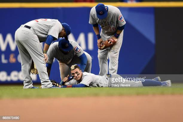 Javier Baez of the Chicago Cubs signals he is ok following a collision with Jason Heyward during the sixth inning of a game against the Milwaukee...