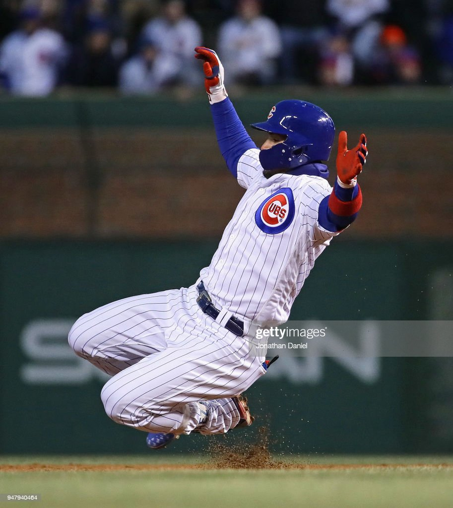 Javier Baez #9 of the Chicago Cubs slides into second base with a double in the 2nd inning against the St. Louis Cardinals at Wrigley Field on April 17, 2018 in Chicago, Illinois.