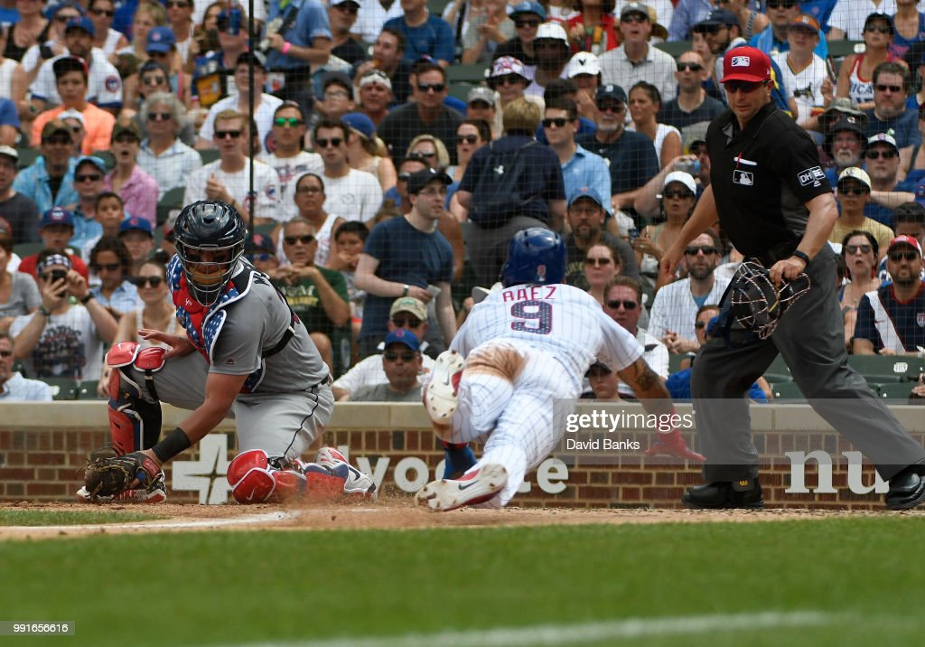 Javier Baez #9 of the Chicago Cubs steals home plate as James McCann #34 of the Detroit Tigers makes a late tag during the fourth inning on July 4, 2018 at Wrigley Field in Chicago, Illinois.
