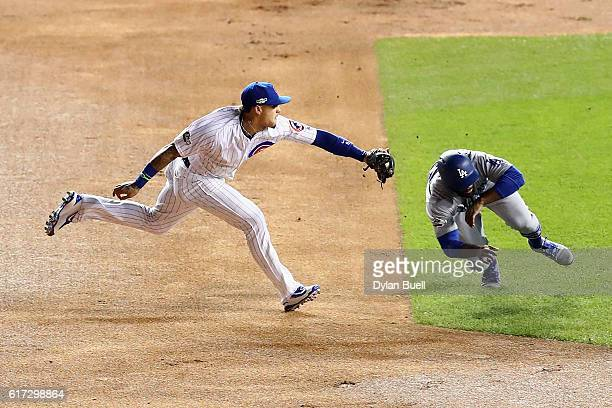 Javier Baez of the Chicago Cubs tags out Andrew Toles of the Los Angeles Dodgers at second base in the first inning during game six of the National...