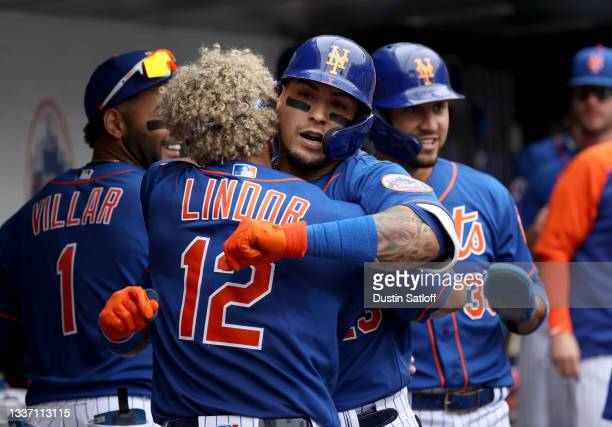Javier Baez of the New York Mets celebrates with Francisco Lindor in the dugout after hitting a two run home run during the bottom of the fourth...