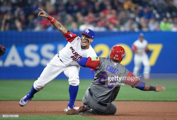Javier Baez the Puerto Rico tags out Nelson Cruz of the Dominican Republic as he tries to steal second base during the eighth inning of the World...