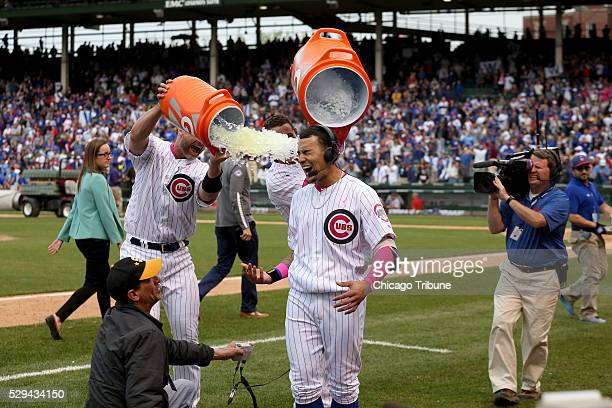 Javier Baez who hit a solo homer in the 13th inning to win the game for the Chicago Cubs is doused with ice by his teammates David Ross and Anthony...