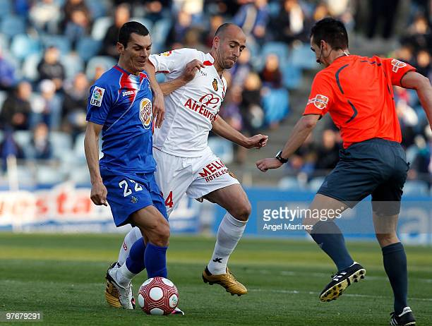 Javier Casquero of Getafe and Borja Valero of Mallorca duel for the ball beside the referee during the La Liga match between Getafe and Mallorca at...