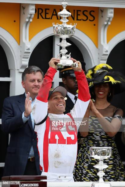 Javier Castellano rider of Cloud Computing celebrates with the trophy alongside Baltimore City Stephanie RawlingsBlake after winning the 142nd...