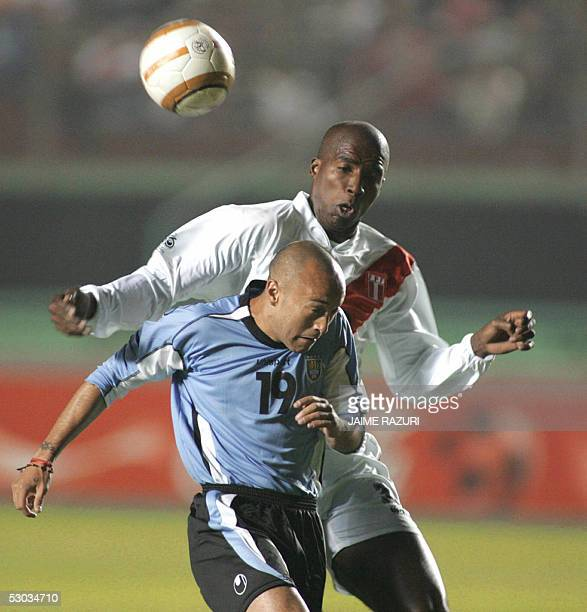 Javier Chevanton of Uruguay fights for the ball with Luis Guadalupe of Peru during their Fifa Word Cup Germany 2006 South American qualifier at the...