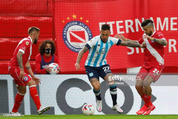 Javier Correa of Racing Club fights for the ball with Elías Gómez of Argentinos Juniors during a match between Argentinos Juniors and Racing Club as...
