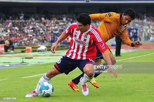 Javier Cortes of Pumas struggles for the ball with Jonny Magallon of Chivas during a match as part Clausura 2012 at Olympic Stadium on January 29...