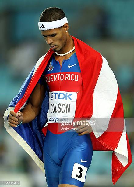 Javier Culson of Puerto Rico walks with his country's flag over his shoulders after claiming silver in the men's 400 metres hurdles final during day...
