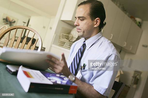 Javier Garcia looks through a book in his apartment before going to work as a psychiatric resident at Long Island Jewish Hospital June 14, 2005 in...