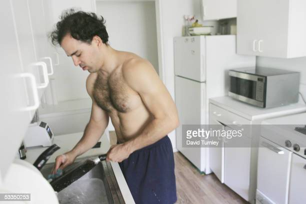 Javier Garcia washes dishes in his apartment June 14, 2005 in New Hyde Park, New York. Javier Garcia, an Argentinian-American and a third-year...