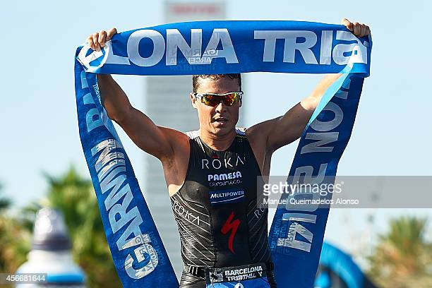 Javier Gomez Noya of Spain crosses the finish line and celebrates his first place win during Garmin Barcelona Triathlon 2014 at Playa de la Mar Bella...