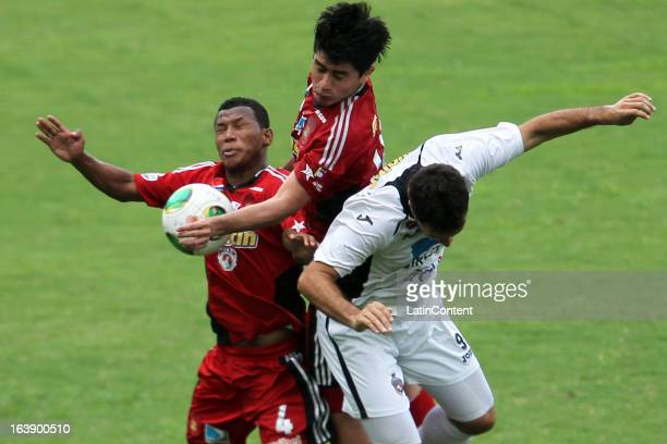 Javier Guarino of Real Esspor fights for the ball with Antonio Da Silva and Andres Sanchez of Caracas FC during the match between Real Esppor Club...