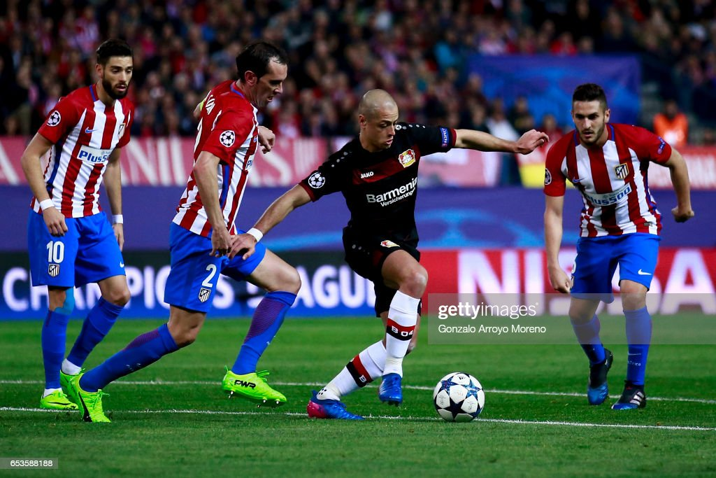 Javier Hernandez alias Chicharito (2ndR) of Bayer Leverkusen competes for the ball with Diego Godin (2ndL), Koke (R) and Yannick Carrasco (L) of Atletico de Madrid during the UEFA Champions League Round of 16 second leg match between Club Atletico de Madrid and Bayer Leverkusen at Vicente Calderon Stadium on March 15, 2017 in Madrid, Spain.