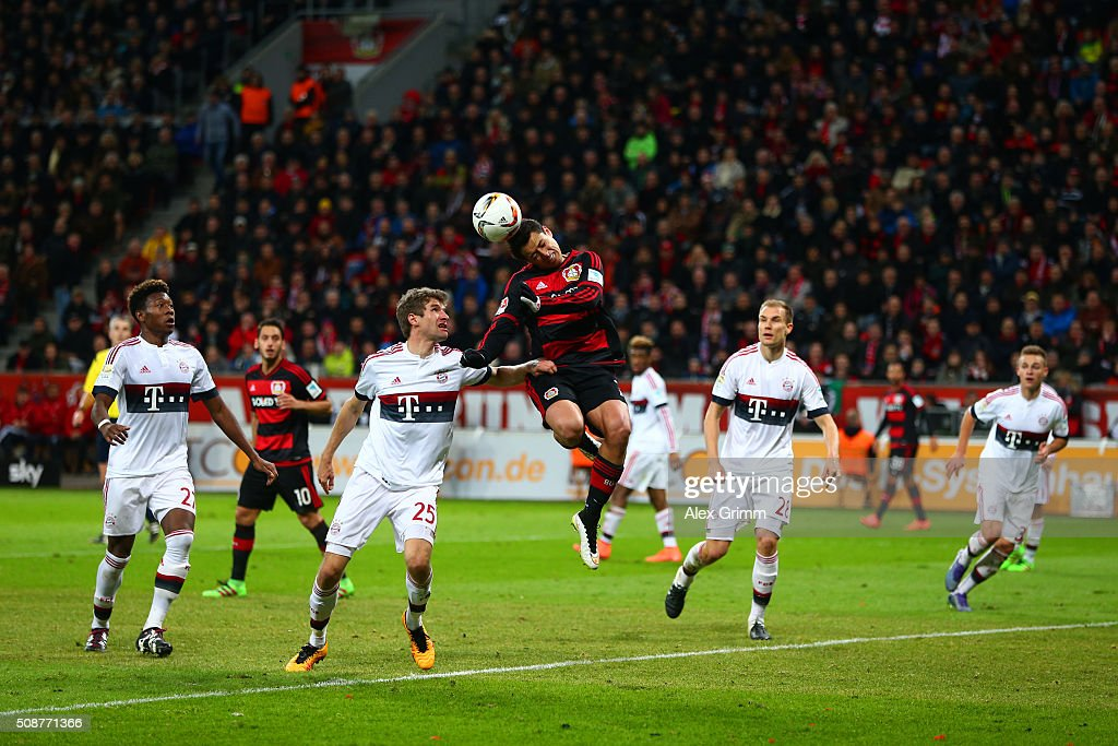 Javier Hernandez of Bayer Leverkusen heads the ball under pressure from Thomas Muller of FC Bayern Muenchen during the Bundesliga match between Bayer Leverkusen and FC Bayern Muenchen at BayArena on February 6, 2016 in Leverkusen, Germany.