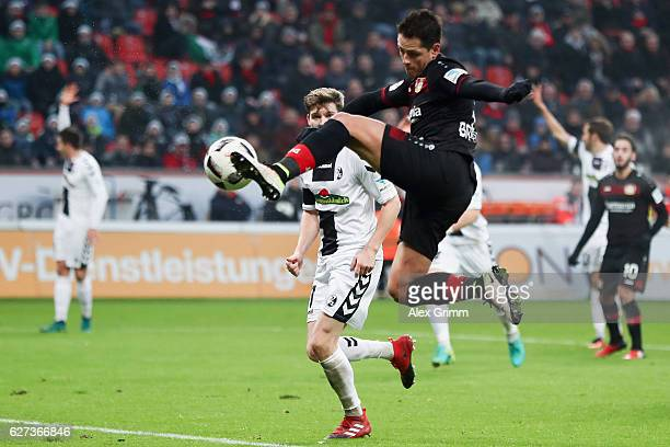 Javier Hernandez of Leverkusen kicks the ball ahead of Lukas Kuebler of Freiburg during the Bundesliga match between Bayer 04 Leverkusen and SC...
