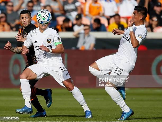 Javier Hernandez of Los Angeles Galaxy heads the ball away from Matias Vera of Houston Dynamo as Joe Corona looks on at BBVA Stadium on February 29...