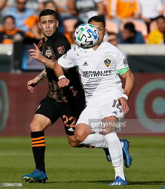 Javier Hernandez of Los Angeles Galaxy keeps his eye on the ball as he is pressured by Matias Vera of Houston Dynamo at BBVA Stadium on February 29...