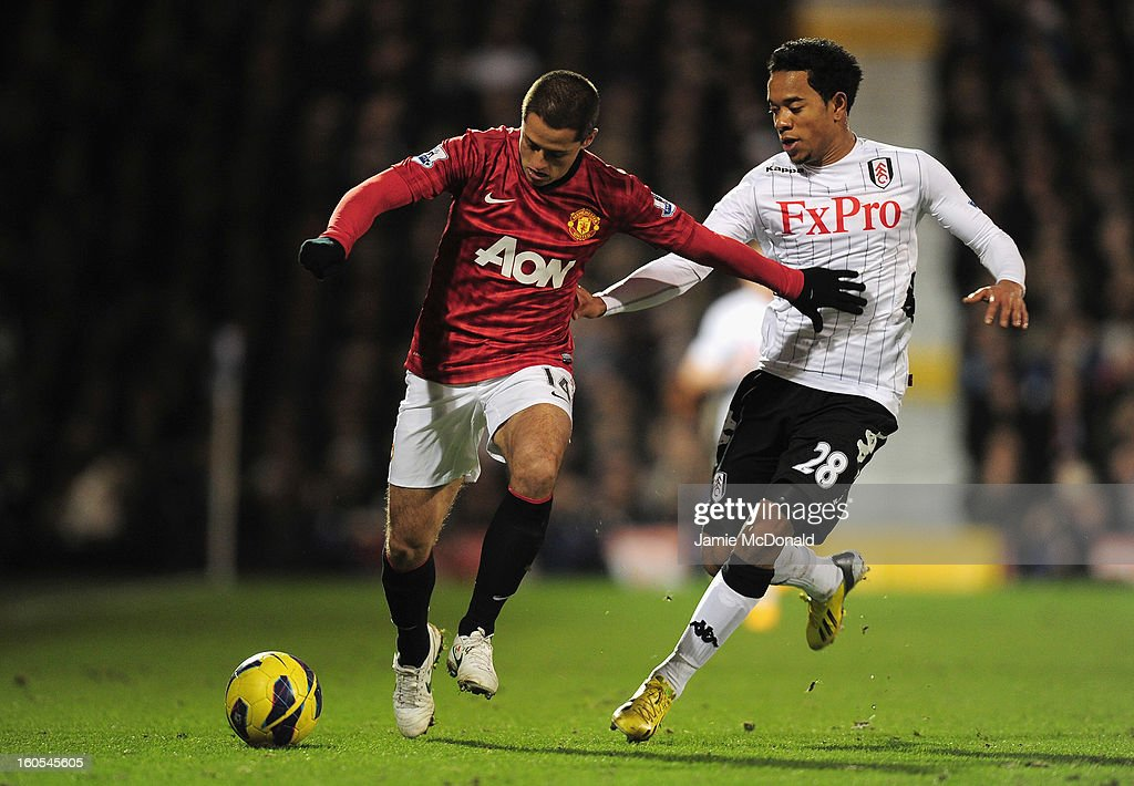 Javier Hernandez of Manchester United and Urby Emanuelson of Fulham tussle for the ball during the Barclays Premier League match between Fulham and Manchester United at Craven Cottage on February 2, 2013 in London, England.