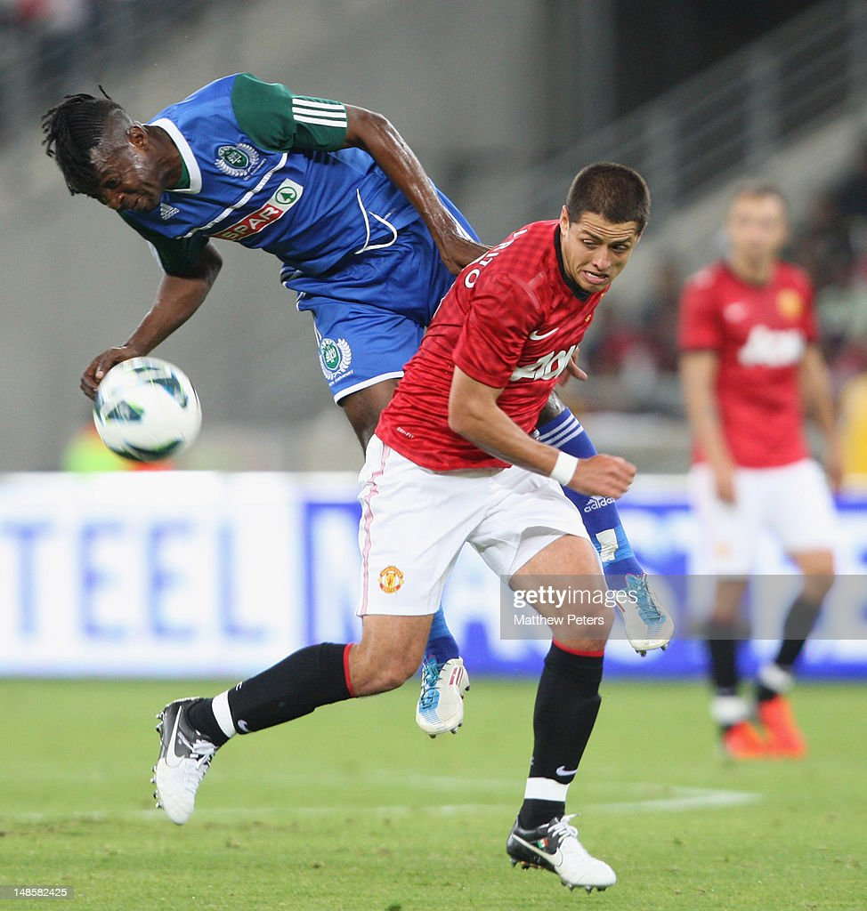 Javier Hernandez of Manchester United clashes with Bukasa Kasonga of AmaZulu FC during the pre-season friendly between AmaZulu FC and Manchester United at Moses Mabhida Stadium on July 18, 2012 in Durban, South Africa.