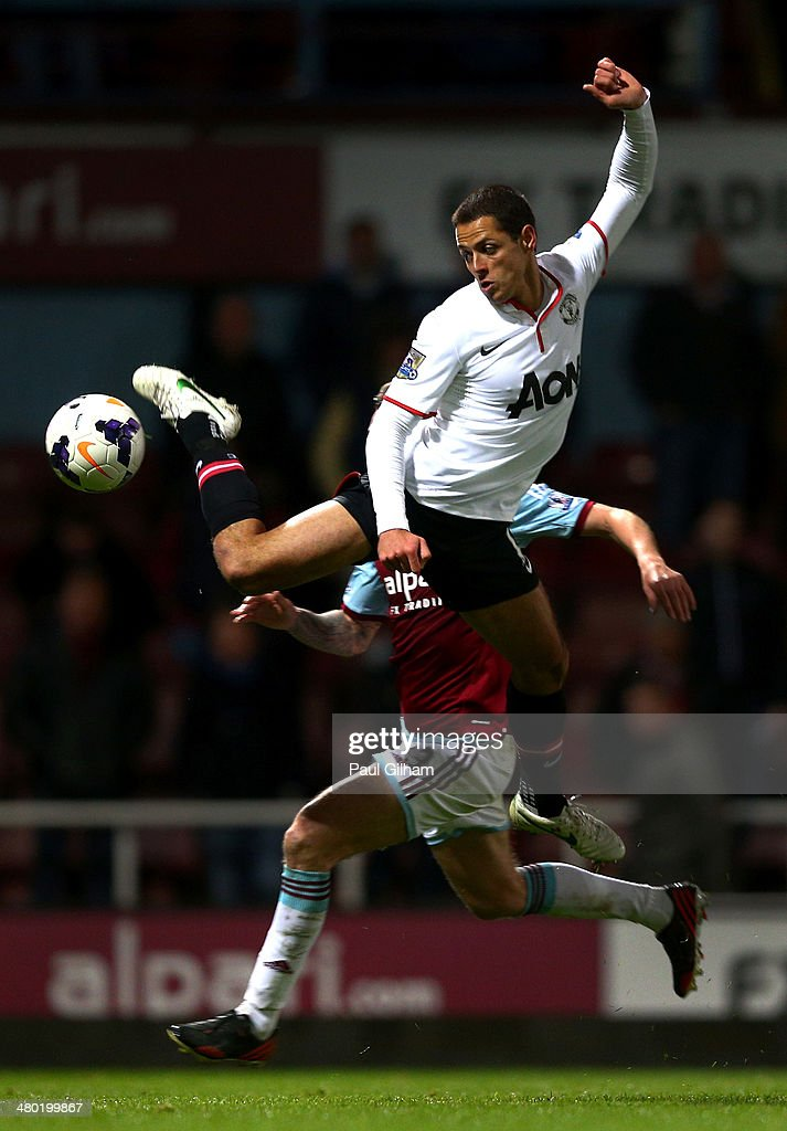 Javier Hernandez of Manchester United competes for the ball with George McCartney of West Ham during the Barclays Premier League match between West Ham United and Manchester United at Boleyn Ground on March 22, 2014 in London, England.