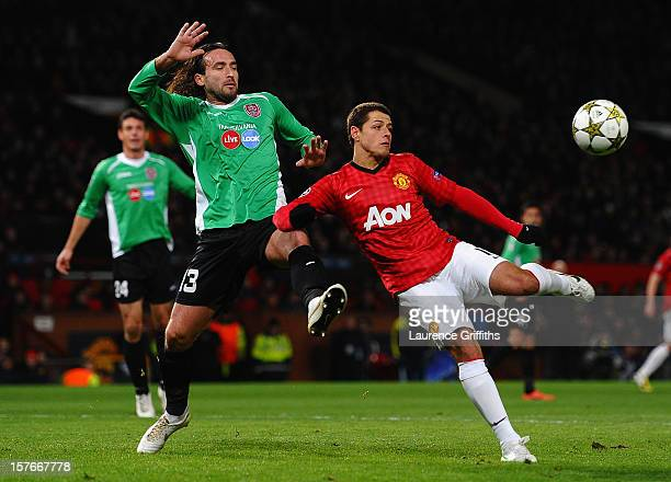 Javier Hernandez of Manchester United competes with Felice Piccolo of CFR 1907 Cluj during the UEFA Champions League Group H match between Manchester...