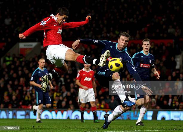 Javier Hernandez of Manchester United shoots at goal under pressure from Robert Huth of Stoke City during the Barclays Premier League match between...