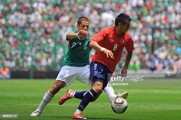 Javier Hernandez of Mexico fights for the ball with Arturo Vidal of Chile during a friendly match as part of the Mexico National team preparation for...