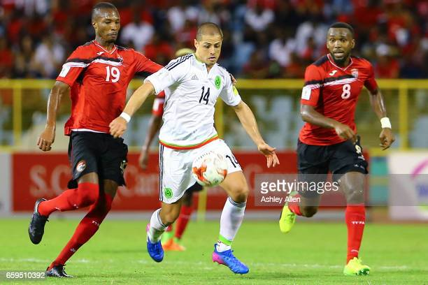 Javier Hernandez of Mexico runs with the ball as Khaleem Hyland and Kevan George of Trinidad look on during the fifth round match between Trinidad...