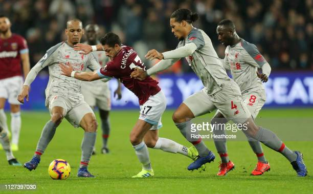 Javier Hernandez of West Ham United battles for possession with Fabinho of Liverpool and Virgil van Dijk of Liverpool during the Premier League match...