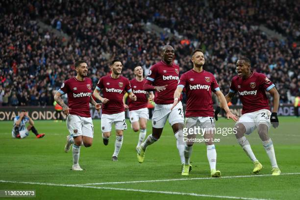 Javier Hernandez of West Ham United celebrates after scoring his team's fourth goal with his team mates during the Premier League match between West...