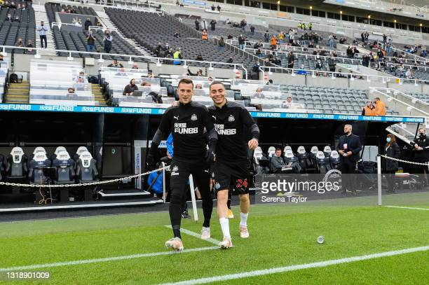 Javier Manquillo of Newcastle United FC and Miguel Almirón walk outside on the pitch to warm up ahead of the Premier League match between Newcastle...